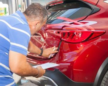 Panel beater assessing car dent - dent removal Albion, Brisbane