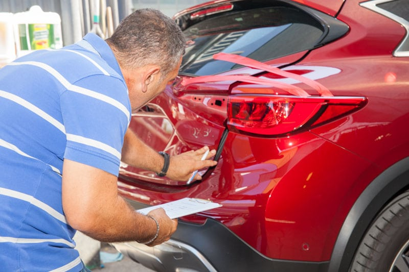 Panel beater assessing car dent - dent removal Albion, Brisbane
